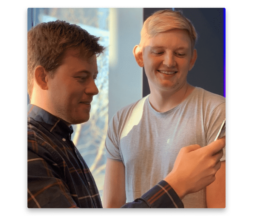 Two guys happily looking at a phone